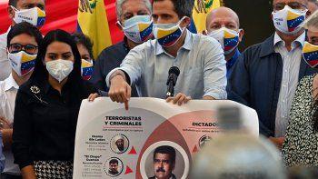 El presidente encargado de Venezuela, Juan Guaidó, con una máscara facial con la bandera venezolana, muestra un cartel que representa al dictador venezolano Nicolás Maduro para expresar sus presuntos vínculos con terroristas, criminales y dictadores, mientras habla durante una conferencia de prensa en la plaza Los Palos Grandes del barrio Chacao. Caracas, el 12 de mayo de 2021.
