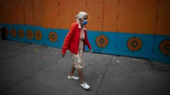 Una mujer mayor, con mascarilla para protegerse del coronavirus, camina por una calle en Caracas, Venezuela, el 17 de julio de 2020, durante la pandemia del coronavirus.