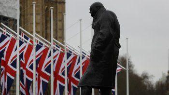 Banderas británicas ondean en el exterior del parlamento británico, cerca de la estatua de Winston Churchill, en Londres, el 30 de enero de 2020, en la víspera de la salida de Gran Bretaña de la Unión Europea.