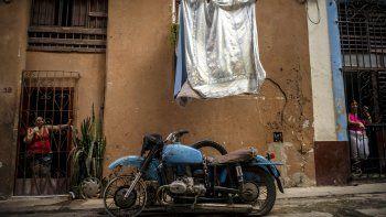 Mujeres miran desde sus puertas delanteras hacia una calle donde una motocicleta con sidecar está estacionada fuera de uso debido a la falta de repuestos, en La Habana, Cuba, el sábado 7 de noviembre de 2020.