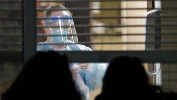 Una trabajadora vestida con una máscara y un traje de protección, vista a través de una ventana en el interior de la habitación de Susan Hailey, de 76 años, quien dio positivo por un nuevo coronavirus, mientras las hijas de la paciente observan desde fuera, el 10 de marzo de 2020, en el Life Care Center en Kirkland, Washington, cerca de Seattle, EEUU.