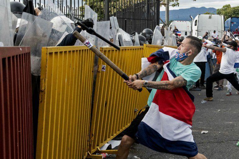 Un manifestante envuelto en una bandera costarricense y con un tubo de metal se enfrenta a la policía antidisturbios durante una protesta contra la moción del gobierno de aumentar los impuestos para llegar a un acuerdo crediticio con el Fondo Monetario Internacional (FMI)