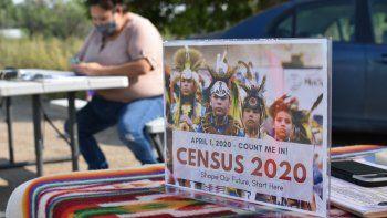 Fotografía de archivo del 26 de agosto de 2020 de un letrero que promueve la participación de los descendientes de las tribus que habitaban el suelo que ahora es Estados Unidos y parte de México y Canadá en el censo de Estados Unidos, junto a una voluntaria, Selena Rides Horse (al fondo), de la tribu Crow Indian en Lodge Grass, Montana.