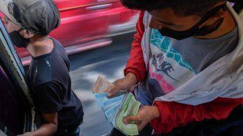 Un trabajador cuenta dinero cuando la gente sube a un autobús turístico interurbano en Caracas el 29 de enero de 2021. El transporte es el único sector que todavía utiliza billetes de bolívar en efectivo, convirtiendo los autobuses en casas de cambio en zonas pobres.