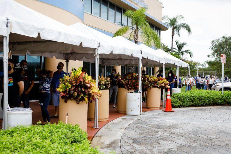 Los votantes esperan en línea para emitir sus primeras boletas en el Departamento de Elecciones del Condado de Miami-Dade en Miami