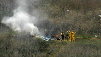 En esta foto del 26 de enero de 2020, los bomberos apagan restos del helicóptero que se estrelló en la localidad de Calabasas, California, causando la muerte del exbasquetbolista Kobe Bryant y de otras ocho personas