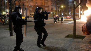 Un miembro de la policía regional catalana Mossos dEsquadra apunta con una escopeta de goma a los manifestantes durante los enfrentamientos tras una manifestación contra el encarcelamiento del rapero español Pablo Hasel en Barcelona el 18 de febrero de 2021. Decenas de personas fueron detenidas en España tras una segunda noche de enfrentamientos por el encarcelamiento de un rapero por tweets controvertidos, lo que desencadenó una reacción política. Las manifestaciones furiosas estallaron por primera vez el 16 de febrero por la noche después de que la policía detuviera a Pablo Hasel, de 32 años, que estaba encerrado en una universidad de Cataluña para evitar ir a la cárcel en un caso de libertad de expresión muy polémico.