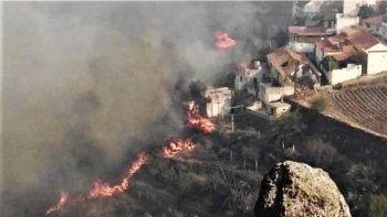 En esta foto difundida por el cabildo de Gran Canaria se ve un incendio cerca de unas casas en El Rincón, en la isla de España, el domingo 18 de agosto de 2019.