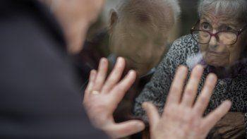 Xavier Antó, de 90 años, habla con su esposa Carmen Panzano, de 92, a través de una ventana en el asilo donde ella vive en Barcelona, España, el 21 de abril de 2021. La casa de ancianos tomó estas medidas para proteger a sus residentes del coronavirus.