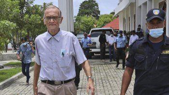 Un agente de policía escolta a Richard Daschbach (izquierda), un exmisionero de Pensilvania, antes de su llegada a un juicio en una corte en Oecusse, Timor Oriental, el 23 de febrero de 2021.