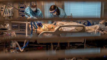 La asistente de aboratorio de flebotomías Jennifer Cukati, a la derecha, y la enfermera Carina Klescewski, a la izquierda, atienden a un paciente de COVID-19 en la UCI del Centro Médico Sutter Roseville Medical Center en Roseville, California, el martes 22 de diciembre de 2020.