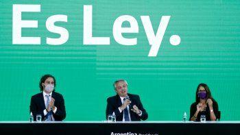 El presidente de Argentina, Alberto Fernández (C), habla junto al Jefe de Gabinete Santiago Cafiero (L) y la Ministra de Mujer, Género y Diversidad, Elizabeth Gómez Alcorta, durante la ceremonia de promulgación de la ley del aborto conocida como Ley de Interrupción Voluntaria del Embarazo (IVE en Español) en Buenos Aires, el 14 de enero de 2021. Fernández firma la ley que permite la interrupción voluntaria hasta las 14 semanas de embarazo, la cual fue aprobada por el Senado el 30 de diciembre de 2020.