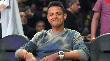 El delantero de Los Angeles Galaxy, Chicharito, posa para la cámara mientras mira durante la primera mitad de un juego de baloncesto de la NBA entre Los Angeles Lakers y los Philadelphia 76ers el martes 3 de marzo de 2020 en Los Ángeles.
