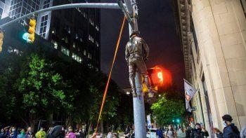 Varios manifestantes cuelgan una estatua tomada del monumento a la Confederación en el Capitolio del estado de un poste en la esquina de las calles Salisbury y Hargett en Raleigh, Carolina del Norte, la noche del viernes 19 de junio de 2020.