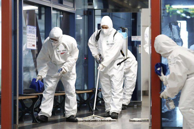 Soldados surcoreanos con trajes de protección desinfectan una zona como precaución contra el nuevo coronavirus