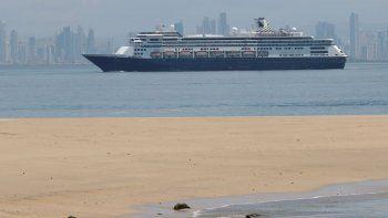 El crucero Zaandam, que transporta a decenas de pasajeros con síntomas similares a la gripe, llega a la bahía de la ciudad de Panamá, vista desde la Isla de Taboga, Panamá, el viernes 27 de marzo de 2020.