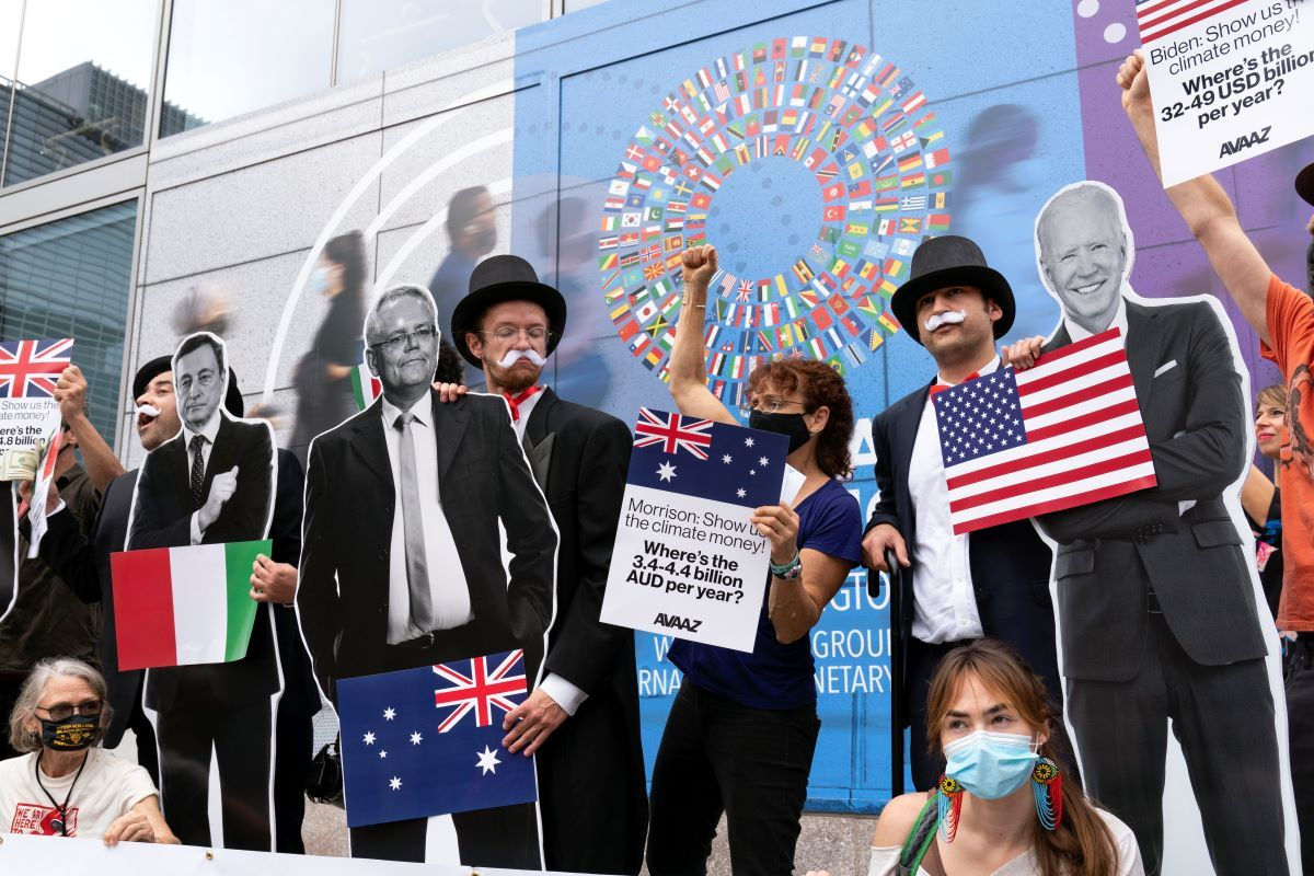 Activistas que sostienen imágenes en cartón del presidente estadounidense Joe Biden, el primer ministro australiano Scott Morrison y el premier italiano Mario Draghi protestan frente a la sede del Fondo Monetario Internacional durante las reuniones anuales entre el FMI y el Banco Mundial, el miércoles 13 de octubre de 2021, en Washington.