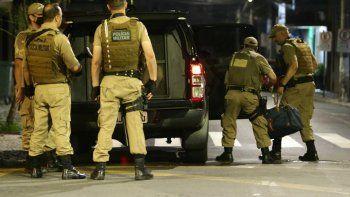 Militares cargan una bolsa llena de dinero que se quedó tras el robo de un banco en Cricuima, estado de Santa Catarina, Brasil, el martes 1 de diciembre de 2020.