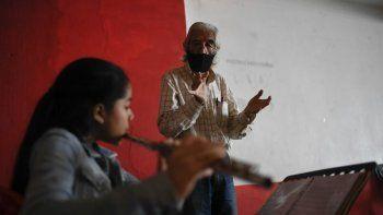 Narciso Ernesto Pichardo, un profesor de música de 75 años, con una mascarilla protectora, da una clase en el Centro Cultural del barrio La Pastora en Caracas el miércoles 19 de agosto del 2020, en medio de la pandemia del coronavirus.