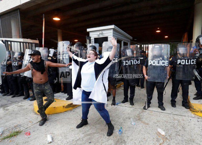 Un par de manifestantes intentan convencer a otros que no arrojen piedras y botellas de agua a la policía durante una manifestación el sábado 30 de mayo de 2020
