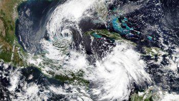 En esta imagen por satélite del 5 de octubre de 2020 proporcionada por NASA Worldview, Earth Observing System Data and Information System (EOSDIS), al tormenta tropical Gamma, a la izquierda, que castigó parte de México durante el fin de semana, y el huracán Delta, abajo a la derecha, que gana fuerza en un rumbo que lo llevará junto a las Islas Caimán el martes por la mañana.