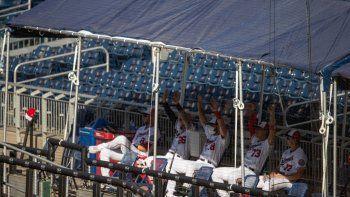 Peloteros de los Nacionales de Washington observan el juego desde el anexo del dugout en las gradas, al enfrentar a los Filis de Filadelfia, el sábado 18 de julio de 2020