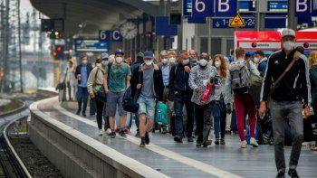 Un grupo de pasajeros con mascarillas para protegerse del coronavirus camina sobre un andén el jueves 24 de junio de 2021 en la principal estación ferroviaria de Fráncfort, Alemania.