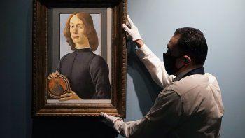 En esta foto de archivo tomada el 27 de enero de 2021, un manipulador de arte de Sotheby's arregla El joven sosteniendo un Roundel de Botticelli durante una vista previa para la prensa en Sotheby's, en Nueva York. El retrato se vendió por 92 millones de dólares, cifra récord para el artista.