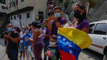 Varias personas usando tapabocas ven pasar la imagen del Nazareno en la Semana Santa, en Caracas, Venezuela, durante la cuarentena por el coronavirus COVID-19.