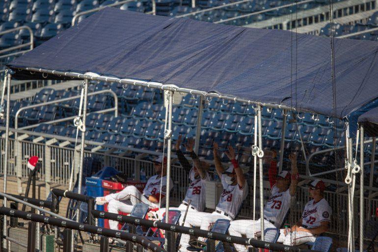Peloteros de los Nacionales de Washington observan el juego desde el anexo del dugout en las gradas