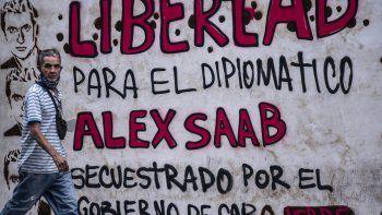 Un hombre pasa junto a un grafiti que dice Libertad para el diplomático Alex Saab, secuestrado por el gobierno de Cabo Verde en Caracas, el 23 de febrero de 2021.