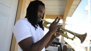 En esta imagen de archivo, tomada el 26 de enero de 2009, el músico Shamarr Allen toca su trompeta, firmada por el quarterback de los Saints de Nueva Orleans Drew Brees, en el porche de su casa en Ninth Ward, Nueva Orleans, donde recientemente grabó el himno del equipo.