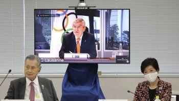 En esta imagen de archivo del 24 de septiembre de 2020, el presidente del COI, Thomas Bach, aparece en la pantalla para intervenir a distancia con el presidente del Comité Organizador Yoshiro Mori, a la izquierda, y la gobernadora de Tokio, Yuriko Koike, a la derecha durante una reunión virtual sobre los aplazados Juegos Olímpicos de Tokio, en Tokio.