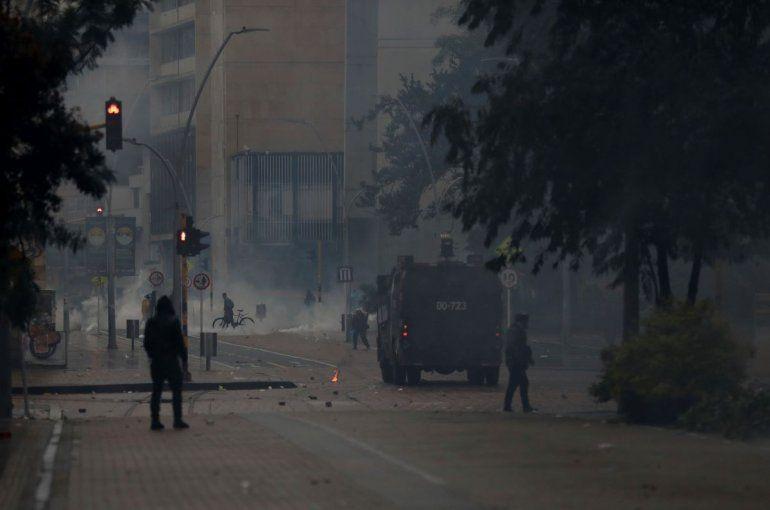 Un vehículo policial antidisturbios conduce después de sacar a los manifestantes de la calle durante los enfrentamientos en Bogotá