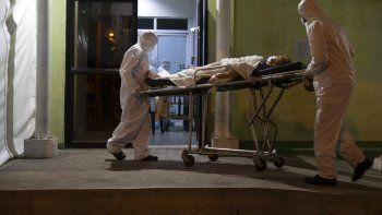 Un paciente con síntomas de COVID-19 es ingresado a un hospital del Seguro Social por bomberos con equipo protector, el viernes 12 de junio de 2020, en Ciudad de Guatemala.