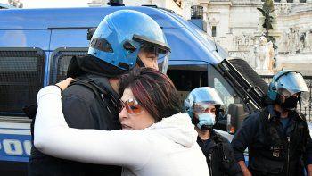 Un manifestante abraza a un oficial de policía en provocación el 15 de noviembre de 2020, en Roma, durante una manifestación antimáscaras y contra las restricciones del gobierno sobre la pandemia Covid-19.