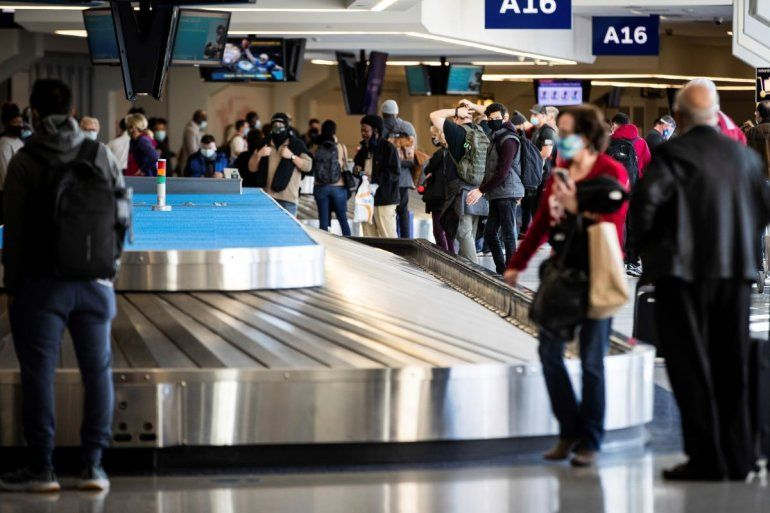 Viajeros esperan su equipaje en el aeropuerto Dallas/Fort Worth el 23 de diciembre del 2020. Casi 1