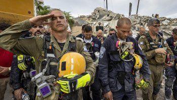 Un miembro del equipo israelí de búsqueda y rescate saluda frente a los escombros del edificio residencial Champlain Towers South, el miércoles 7 de julio de 2021, en Surfside, Florida.