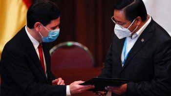El presidente electo Luis Arce, a la derecha, recibe sus credenciales presidenciales de manos del presidente del Tribunal Supremo Electoral, Salvador Romero, durante una ceremonia en La Paz, Bolivia, el miércoles 28 de octubre de 2020.