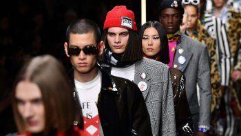 Versace desfigura las prendas elegantes dotándolas de elementos modernos como broches y estampados pop, y conjunta los abrigos ejecutivos con ribetes con plumas naranjas o rosas.