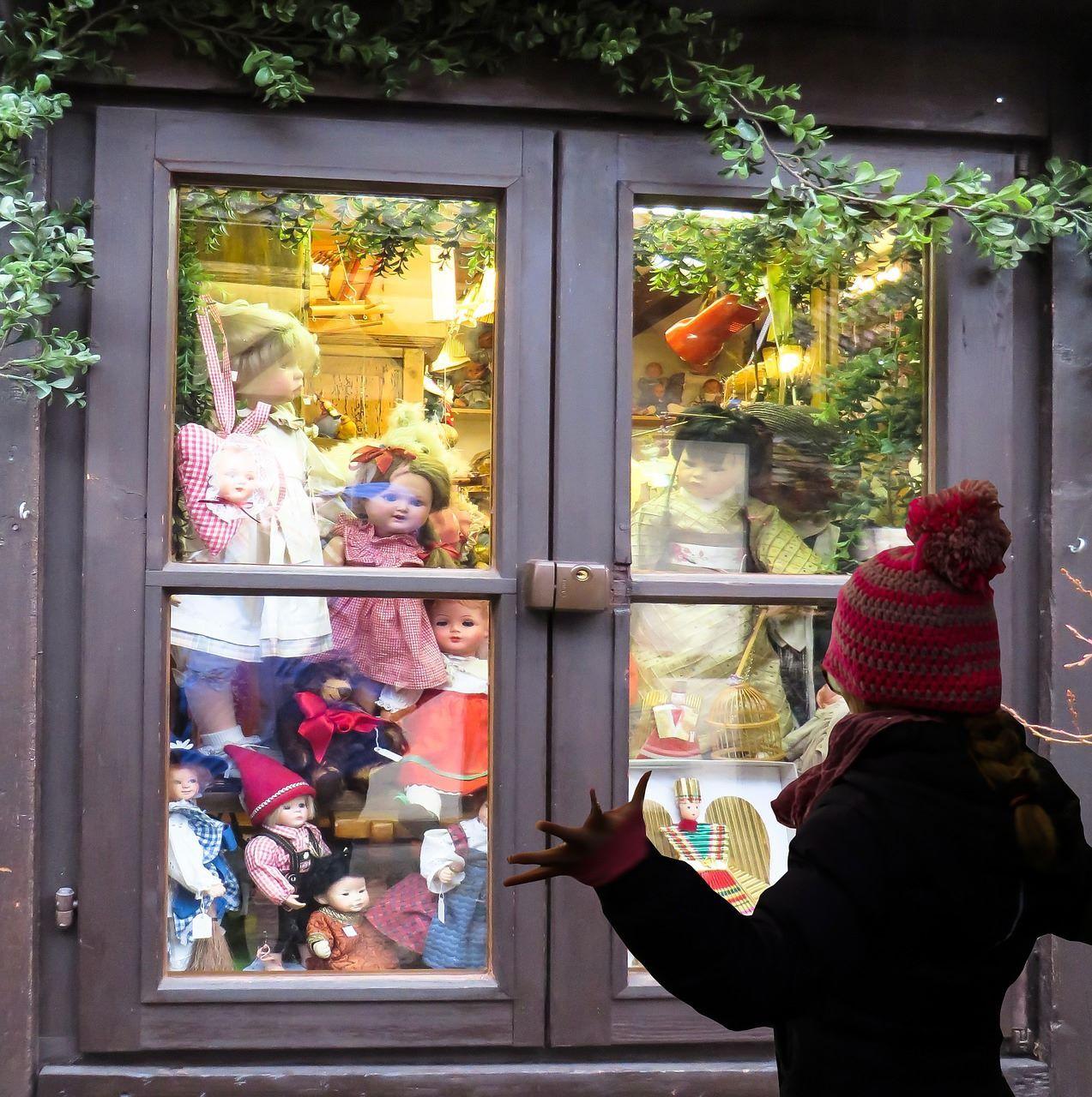 Niña observa juguetes en una tienda a través de una ventana.