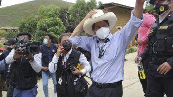 En esta foto difundida por la agencia de noticias peruana Andina, el candidato presidencial del partido Perú Libre, Pedro Castillo, saluda a los simpatizantes después de emitir su voto en las elecciones generales en Cajamarca, Perú, el domingo 11 de abril de 2021.