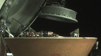 En esta imagen sin fecha distribuida por NASA, un contenedor de muestras sobrevuela una cápsula en la nave espacial Osiris-Rex cerca del asteroide Bennu. La cápsula regresará a Tierra con escombros del asteroide.