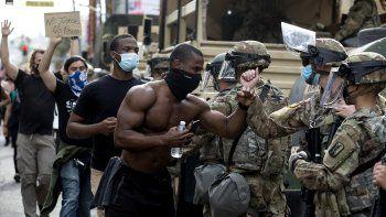 Manifestantes saludan a miembros de la Guardia Nacional mientras marchan por el Bulevar de Hollywood, el martes 2 de junio de 2020 en Los Ángeles, California.