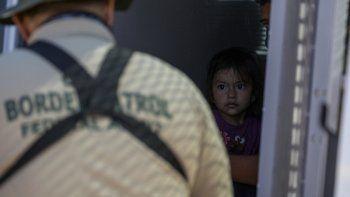 Una joven migrante desde el interior de una camioneta mientras un agente de la Patrulla Fronteriza recopila información de sus padres, en la frontera entre Estados Unidos y México el 12 de mayo de 2021 en Yuma, Arizona.