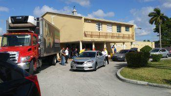 """Vecinos de Sweetwater acuden a recoger alimentos, que son entregados por el comisionado condal José """"Pepe"""" Díaz y el alcalde de Sweetwater, Orlando López, junto a otros funcionarios públicos."""