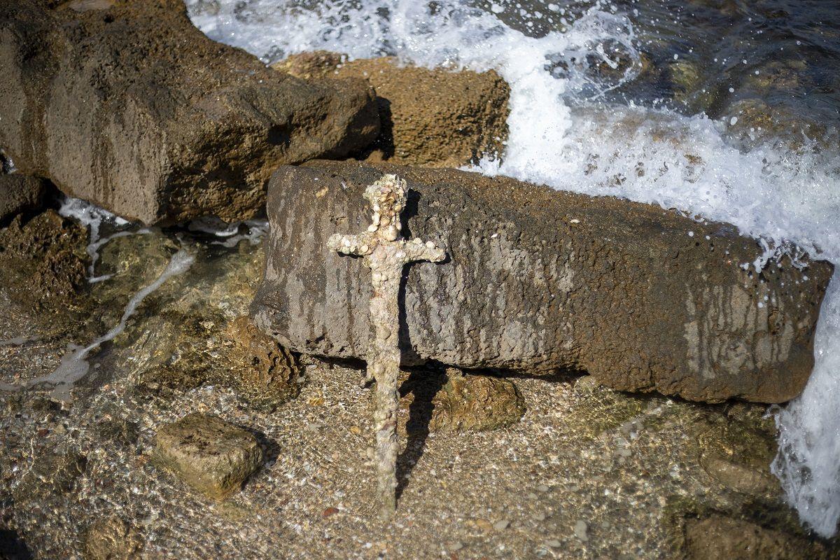 Una espada de un metro (yarda) de largo, que según los expertos pertenece a la época de las Cruzadas, apoyada contra una roca en la ciudad portuaria de Cesarea, Israel, el 19 de octubre de 2021.