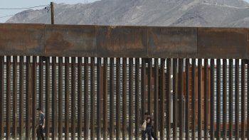En esta foto del 17 de julio del 2019, tres migrantes que evadieron a la Guardia Nacional de México y cruzaron el Río Grande hacia Estados Unidos caminan junto a una barrera fronteriza instalada cerca de la frontera geográfica en El Paso, Texas.