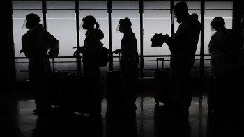 Pasajeros extranjeros con equipos de protección se preparan para viajar a China desde el aeropuerto internacional de Manila, Filipinas, el lunes 18 de enero de 2021.