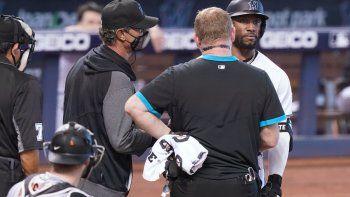 El mánager de los Marlins de Miami Don Mattingly y un entrenador hablan con el bateador Starling Marteantes de ayudarle a salir en el encuentro ante los Gigantes de San Francisco el domingo 18 de abril del 2021.